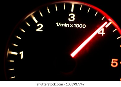 Rev counter, with a red indicator, of a moderately modern car.