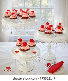 Rev velvet cupcakes decorated with red roses and hearts on 3 tier cakestand.