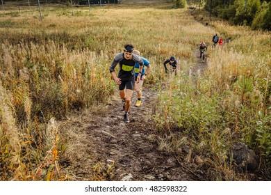 Revda, Russia - September 10, 2016: group of men runners skyrunners running uphill trail in grass during marathon Vertical kilometer