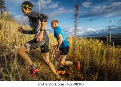 Revda, Russia - September 10, 2016: two men runners skyrunners running uphill trail in grass on blue sky background during marathon Vertical kilometer