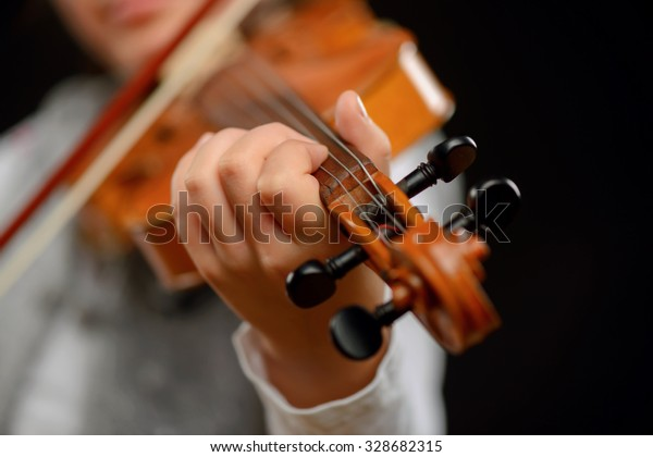 Revel in the sound. Close up of professional violin in hands of little girl holding it and playing while standing isolated on black background