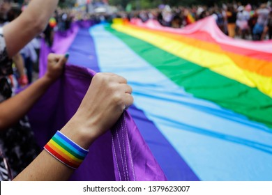 Revelers at the annual gay pride parade hold up a giant rainbow flag in Paulista avenue, Sao Paulo, Brazil.