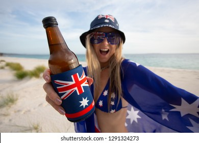 A revelling woman holding a beer on the beach celebrates Australia Day or supports Australian sport enthusiast fan. Beach culture or Aussie holiday.  Focus to bottle
