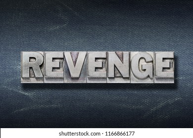 revenge word made from metallic letterpress on dark jeans background