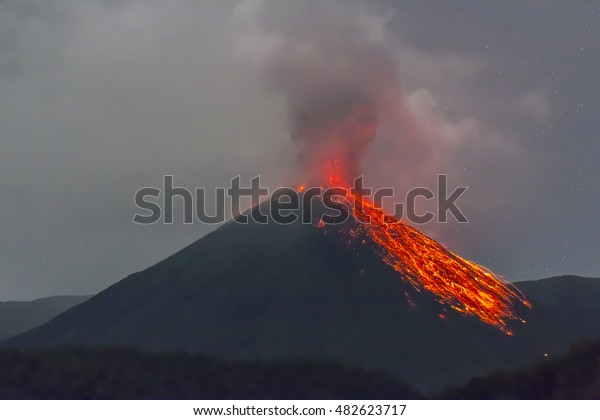 Reventador Volcano, Ecuador erupting at night. Red hot rocks are rolling down the east slope of the mountain. Reventador rises out of tropical rainforest in the Ecuadorian Amazon.