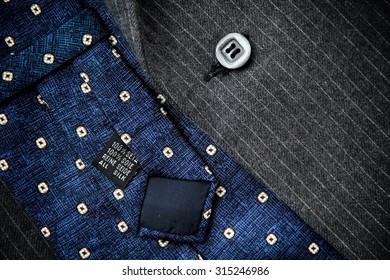 Reverse of blue silk tie with men's black woolen suit.