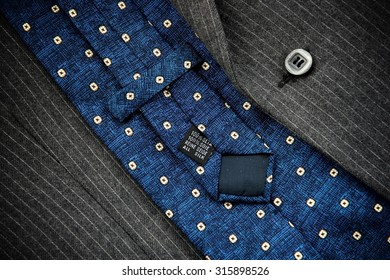 Reverse of blue silk tie with men's black suit.