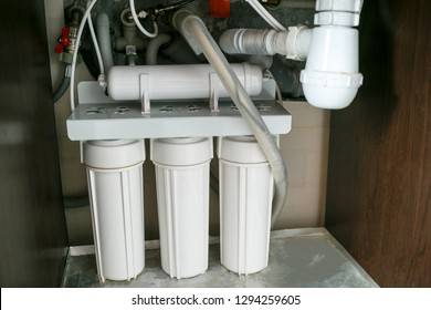 Reverse osmosis water purification system at home. Installation of water purification filters under kitchen sink in cupboard. Clear water concept