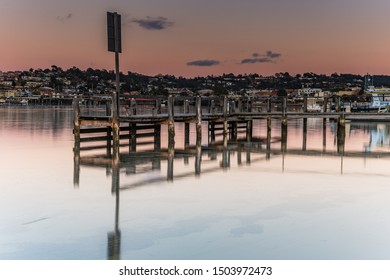 Reverse Sunrise Waterscape with Wharf at Boogy Creek, Merimbula Lake, Merimbula on the South Coast of NSw, Australia.