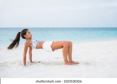 Reverse table top pose in Yoga. Advanced fitness training exercise workout girl on beach exercising core and arm muscles, posture that stretches the front body. Asian woman outside.