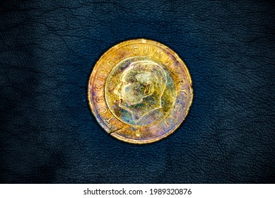 Reverse of used, old and damaged Turkish 1(one) lira coin, minted in 2009, on black leather background. Portrait of Mustafa Kemal Ataturk.