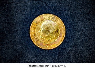 Reverse of used and old Turkish 1(one) lira coin, minted in 2009, on black leather background. Portrait of Mustafa Kemal Ataturk.