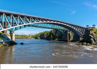 The Reversing Falls bridge in Saint John, New Brunswick, Canada, over the Saint John river. River slowly flowing outward. Train bridge behind, blue sky above. Low angle view.