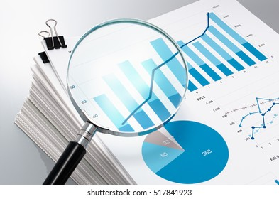 Reviewing and analyzing business reports. Magnifying glass and pile of documents.
