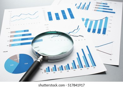 Reviewing business reports. Graphs and charts. Financial reports, documents and magnifying glass.