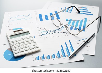 Reviewing business reports. Graphs and charts. Financial reports, documents, calculator, glasses and pen.