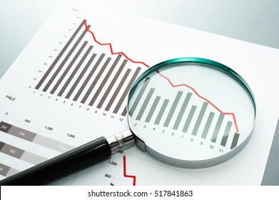 Reviewing financial report. Looking at decrease chart with magnifying glass. Document, chart and magnifying glass on gray reflection background.