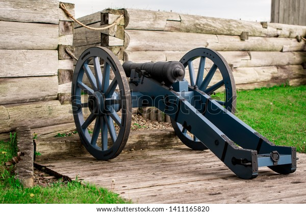 A Revolutionary War Cannon facing the battlements of a wooden wall at Fort Stanwix.
