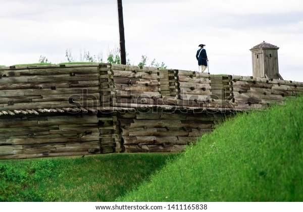 A Revolutionary War Soldier stands on the battlements facing the guard shack on the wooden wall and battlements of Fort Stanwix