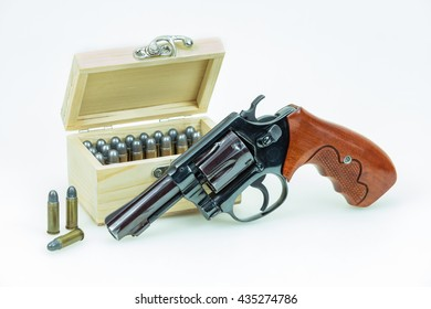revolver gun with bullets isolated on wooden background.