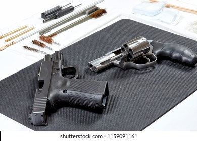 A revolver and a handgun laying on a pad in preparation for cleaning