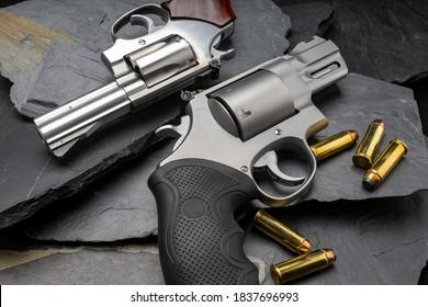 Revolver handguns on black stone background
