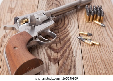 A revolver on a piece of wood.