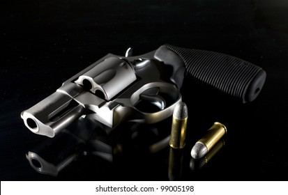 Revolver that is on a black background with side lighting