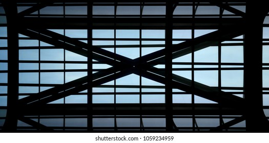 Reworked photo of modern architecture. Underside view of X-shape structural glass ceiling fragment with crossing metal girders / beams
