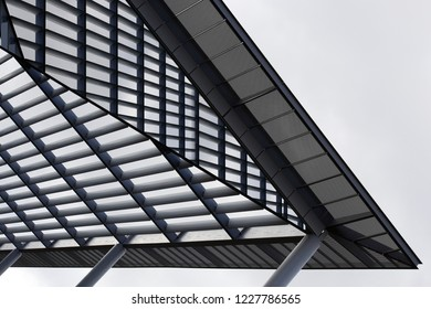 Reworked photo of office building exterior fragment featuring roof with louvered and grid structures. Abstract image on the subject of modern architecture, construction industry or technology.