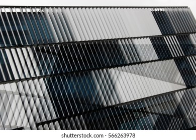 Reworked photo of office building exterior with ajar blinds / jalousie / louvers on windows. Abstract background with louvered structure. Modern architecture, technology or industry motif