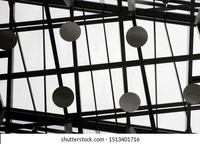 Reworked photo of transparent ceiling with metal framework and round lighting fixtures in an office building. Abstract black and white modern architecture background with geometric structure.