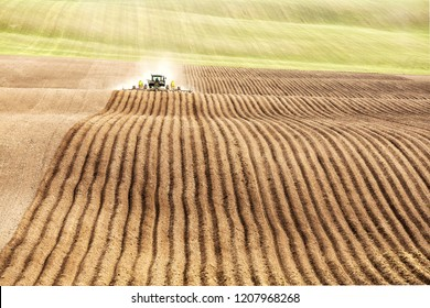 Rexburg, Idaho, USA Apr. 17, 2015 A farmer and tractor in the field planting potatoes in the fertile farm fields of Idaho.