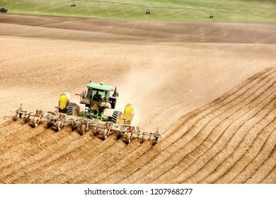 Rexburg, Idaho, USA Apr. 17, 2015 A farmer and tractor in the field planting potatoes in the fertile farm fields of Idaho.