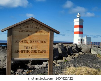 Garður, Reykanes / Iceland - 04/28/2018: The Old Lighthouse Cafe (Flossin - Kaffihus) Sign and Lighthouse, located on the Reykanes Peninsula in Iceland.  Blue sky, ocean, and lava rocks in view.