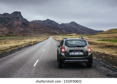 Reykjanes Peninsula, Iceland - June 13, 2016: Car on the straight asphalt road among rocky volcanic landscape on a cloudy summer day