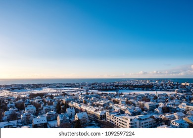Reykjavik downtown in a golden evening light. Capital city of Iceland Reykjavik in winter surrounded with snow covered mountains.