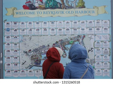 Reykjavik / Iceland - February 6th 2019: Two people study the map to find their way around the old harbour in the icelantic capital city.