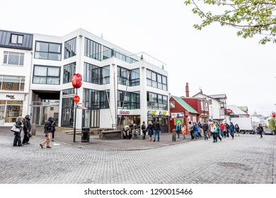 Reykjavik, Iceland - June 19, 2018: Street road sidewalk intersection in downtown center and signs for restaurant deli with many people tourists walking