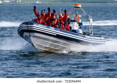 REYKJAVIK, ICELAND - JUNE 3, 2017: Whale and puffin tour boat in full speed in the Atlantic ocean with group of tourists and guide wearing in overalls and life jackets outside Reykjavik.