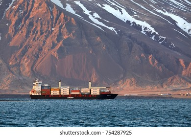 REYKJAVIK, ICELAND - MAY 03, 2015: Container ship arriving in front of majestic mountain landscape. Vessel of Eimskip, oldest shipping company of Iceland.