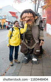 Reykjavik, Iceland - October 12, 2017: man tourist picking nose of troll figure. Happy man with clay figure of troll. Tourist attraction. Popular tourist destination. Hes my lucky troll.