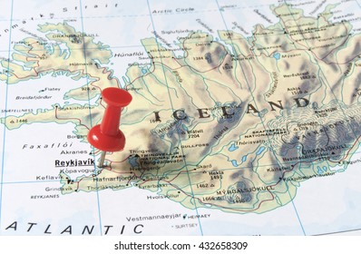 Reykjavik marked with red pushpin on map. Selected focus on Reykjavik and bright red puspin. Pushpin is in an angle. Most parts of Iceland can be seen on map.