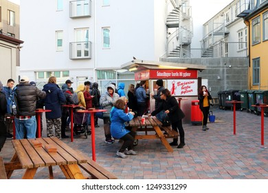 Reykjavik/Iceland - 2 Nov 2018: Customers queuing for and enjoying the hot dogs from Baejarins beztu pylsur (English: The best hot dog in town) hot dog stand in the outdoor