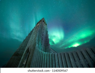 Reykjavik,Iceland-March-13-2018, Perspective of Hallgrimskirkja, The lutheran Church in Iceland with Green aurora borealis and northern light in background.it is powerful and magnificant scene