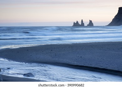 Reynisdrangar sea stacks at sunset, Vik, Iceland, with black sand beach in foreground