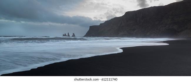 Reynisdrangar sea stacks from Vik beach showing black sand, waves and blue sky.