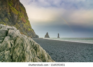 Reynisfjara black sand beach with amazing columnar basalt formations, a vaulted covern, and sea rock stacks visible from the beach in Sound Iceland