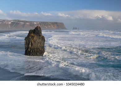 Reynisfjara black sand beach and Reynisdrangar basalt sea stacks as seen from Dyrholaey near Vik, Iceland