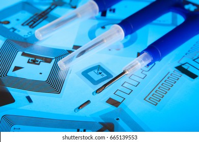 RFID implantation syringes and chips on RFID tags (Radio Frequency Identification tags), blue background
